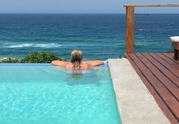 woman in negative rim flow swimming pool overlooking ocean